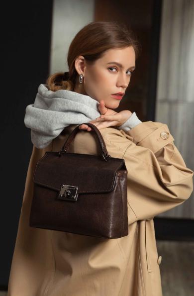 Femme habillée avec un veste oversize et un sac a main en cuir chataigne