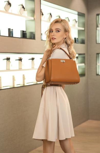 Femme élégante dans une boutique avec un sac a main en cuir
