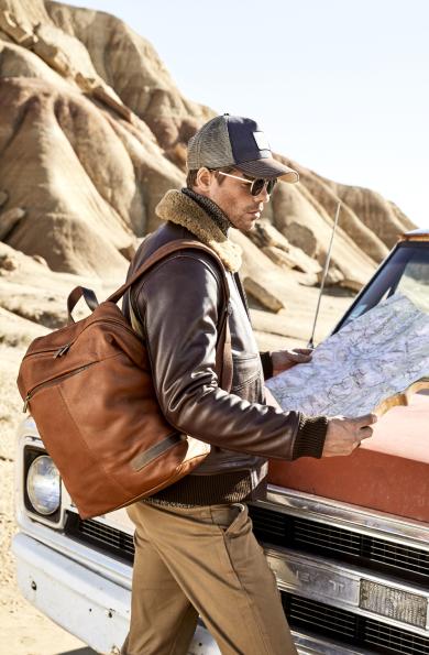 Voyageur avec un sac a dos en cuir marron