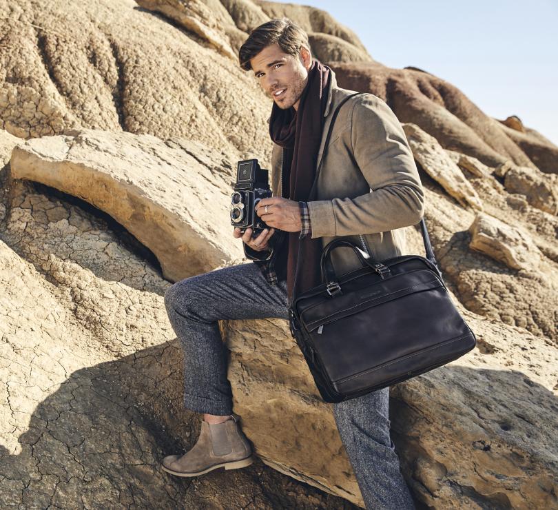 Photographe dans le desert avec un sac de voyage noir